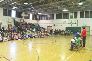Students, staff, and veterans gather in the NRWE gym for an assembly
