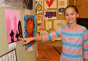 Reilly Batzold, a sixth-grader at Leavenworth Middle School, shows off the painting she created.