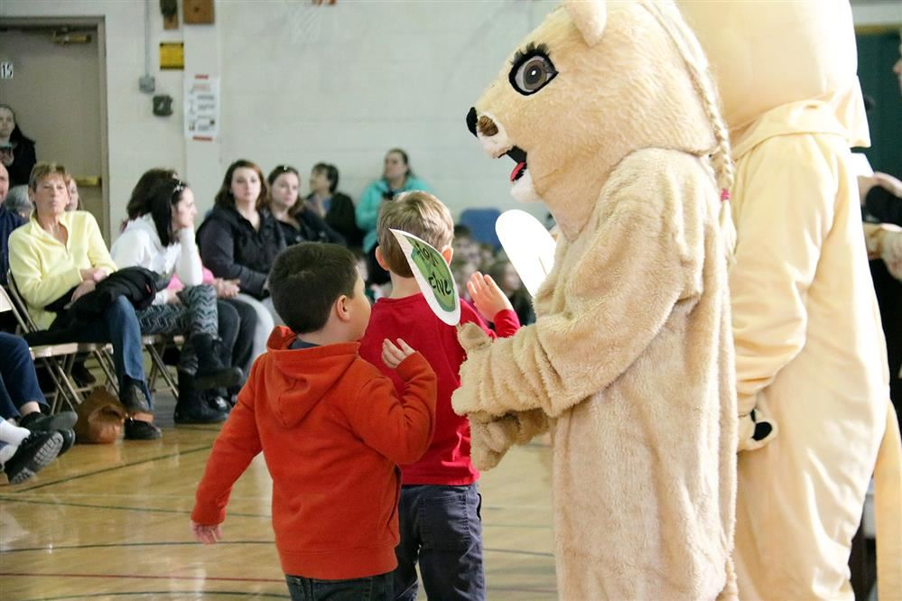 Students give a high five to the school mascot.