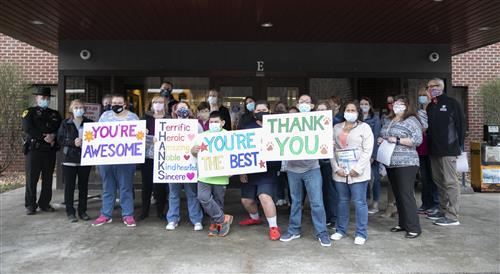 Students hold up signs with Wayne County Public Health staff