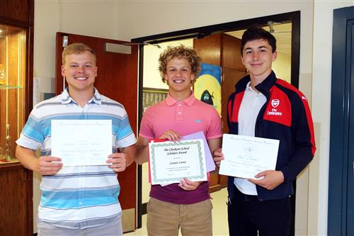 Three male students receive academic awards.